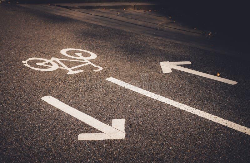 Cykla tecknet och pilar på vägen Vit målad cykel på asfalt Ekologisk grön stads- transport arkivbilder