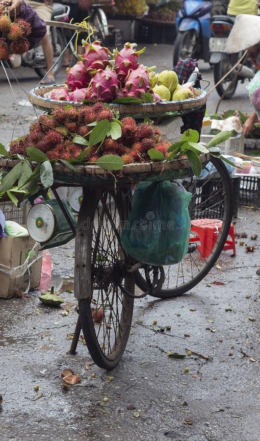 Cykla transportera tropiska frukter på en marknad i Hanoi tävlar in royaltyfri fotografi