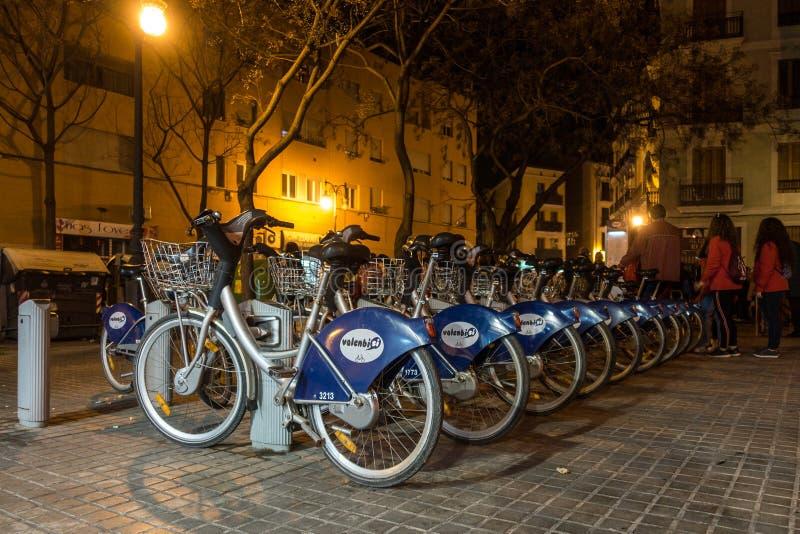 Cyklar för hyra på natten i Valencia Spain på Februari 24, 2019 Oidentifierat folk arkivbild