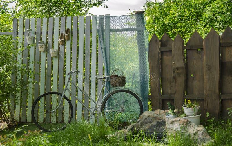 Cyklar i trädgården på bakgrunden av ett träd fäktar royaltyfri foto