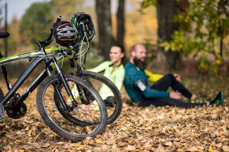 Cyklar och par av cyklister parkerar in royaltyfria bilder