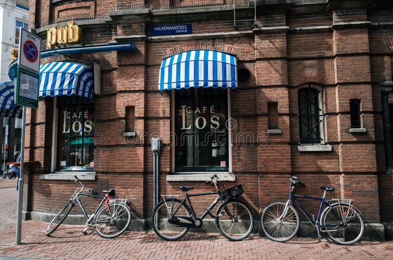 Cyklar parkerade nära kafét i mitt av Amsterdam, Nederländerna arkivfoton