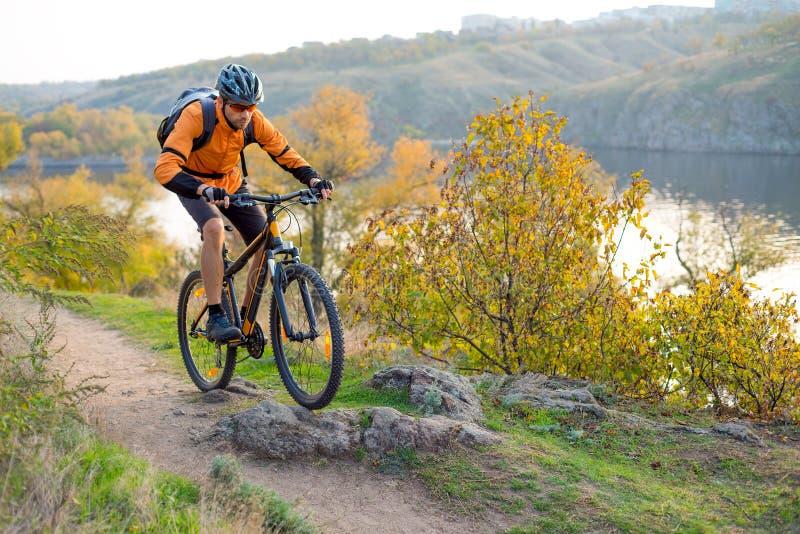 Cyklist i apelsin som rider mountainbiket på Autumn Rocky Trail Extrem sport och Enduro som cyklar begrepp arkivfoton