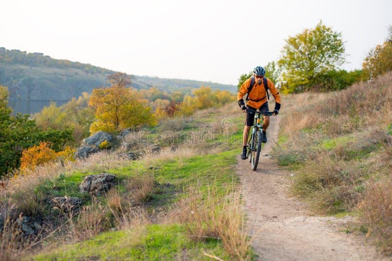 Cyklist i apelsin som rider mountainbiket på Autumn Rocky Trail Extrem sport och Enduro som cyklar begrepp arkivbild
