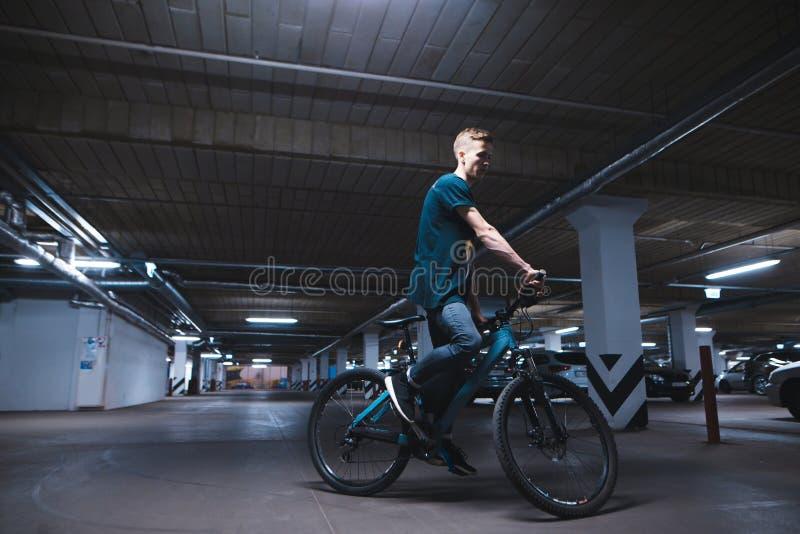 cyklist i en underjordisk parkeringsplats för bilar En man rider en cykel, genom att parkera fotografering för bildbyråer