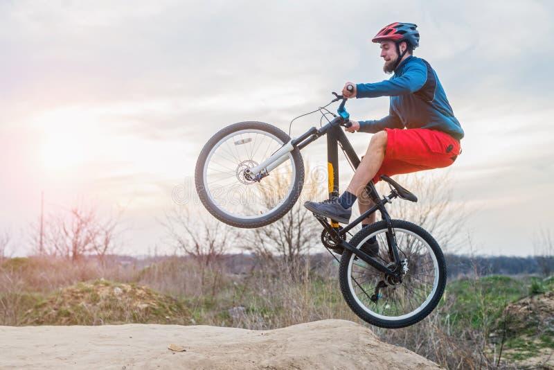 Cyklist i ett blått omslag som rider en cykel Cykla en man som rider mtb royaltyfria foton