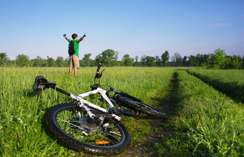 Cyklist i grönt sommarfält arkivfoto