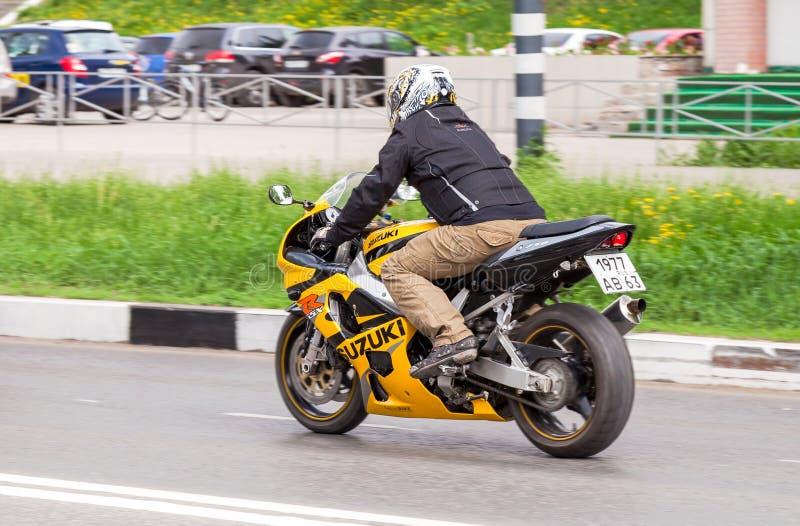 Cyklist i hjälm på en motorcykel Suzuki som springer på vägen i cit arkivbild