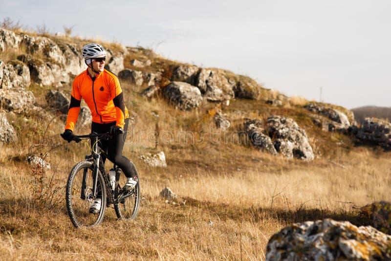 Cyklist i orange omslag som rider cykeln på Rocky Trail Extremt sportbegrepp Utrymme för text royaltyfria bilder