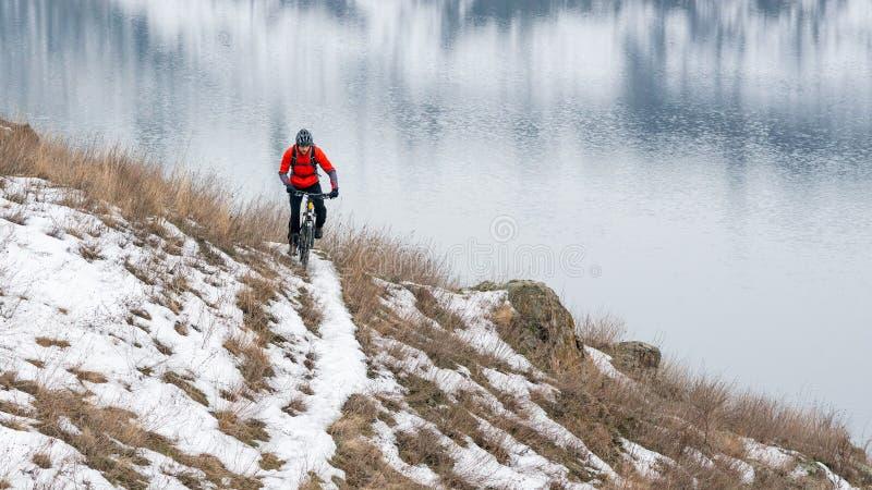 Cyklist i röd ridningmountainbike på den snöig slingan Extrem vintersport och Enduro som cyklar begrepp royaltyfri foto