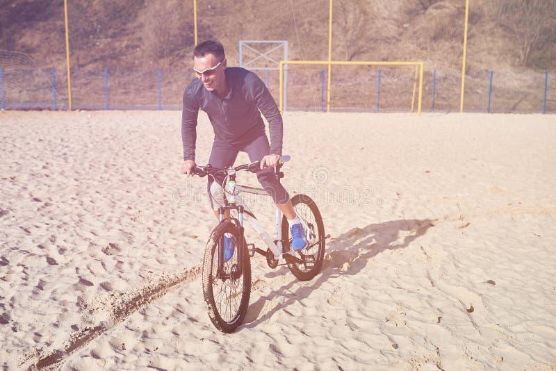 Cyklist med cykeln på sanden arkivfoton
