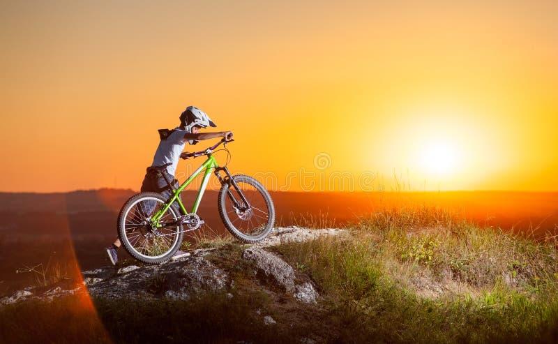 Cyklist med mountainbiket på kullen i aftonen arkivbild