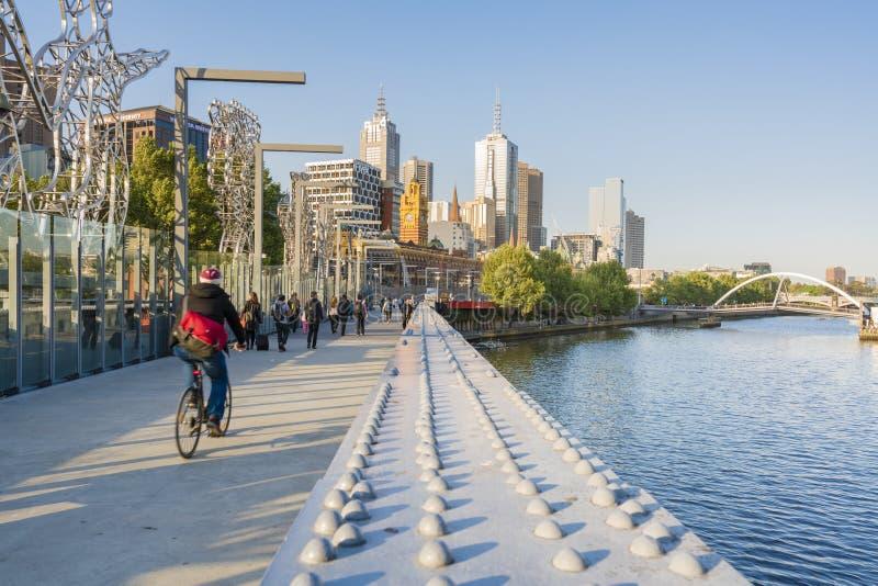Cyklist och folk som in går över en bro royaltyfri bild