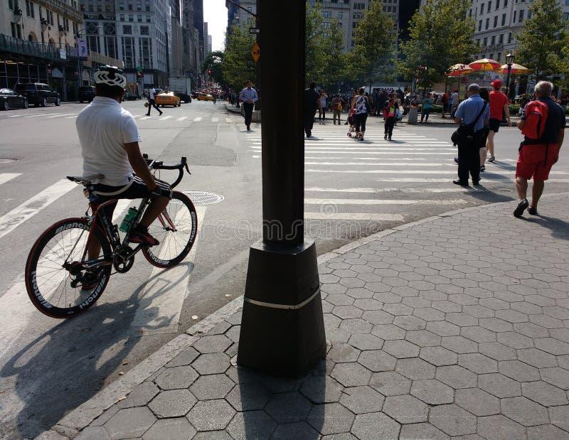 Cyklist och gångare på hörnet av den 5th aveny- och tusen dollararméplazaen, nära Central Park, New York City, NYC, NY, USA royaltyfri foto