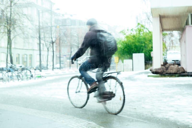Cyklist på snöig dagkontur på iskall dagpendling royaltyfri bild
