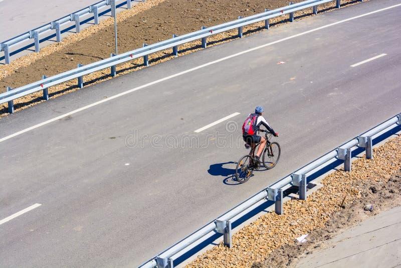 Cyklist på stadsvägen med ingen trafik arkivfoton