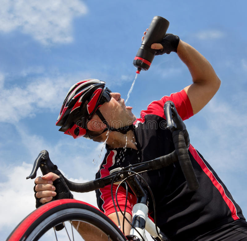 Cyklist som dricker från en flaska royaltyfri foto