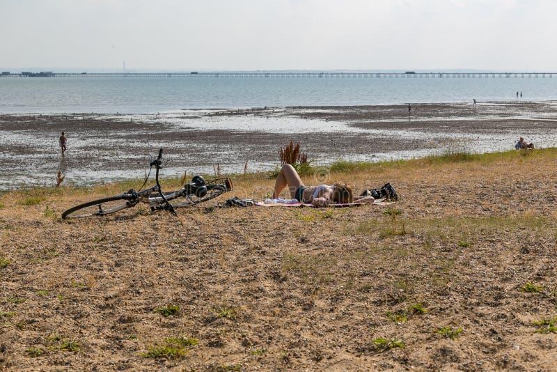 Cyklist som ligger på den Southend stranden på en varm solig dag royaltyfria foton