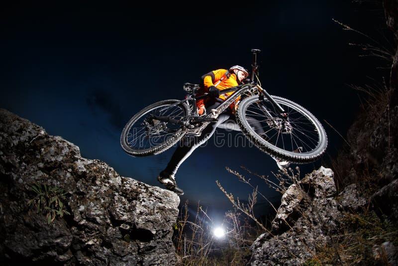 Cyklist som ner rider kullen för cykel på berget Rocky Trail på solnedgången extrema sportar arkivbild