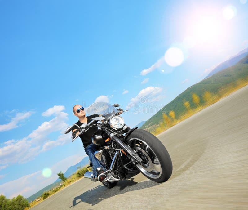 Cyklist som rider en skräddarsy motorcykel på en öppen väg royaltyfri bild