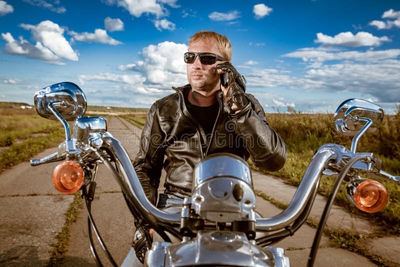Cyklist som talar på en smartphone fotografering för bildbyråer
