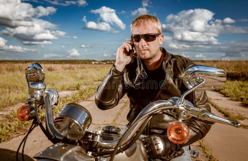 Cyklist som talar på en smartphone royaltyfri bild