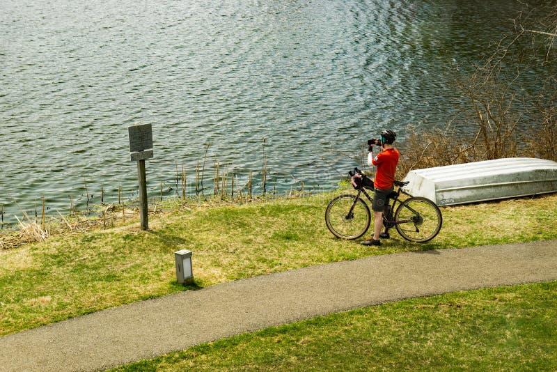 Cyklist som tar ett foto av Abbott sjön och det skarpa bästa berget arkivbilder