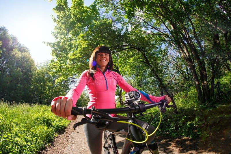Cyklista kobieta jedzie bicykl w parku obraz royalty free