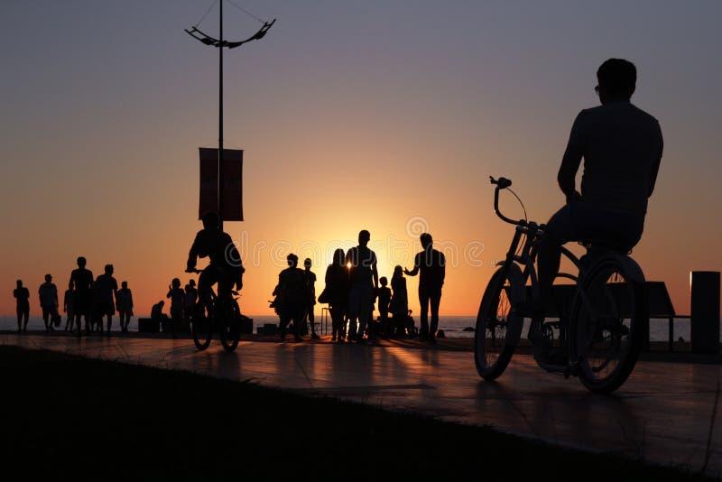 Cyklista sylwetka na morze plaży tłoczył się zmierzchu tło obraz stock