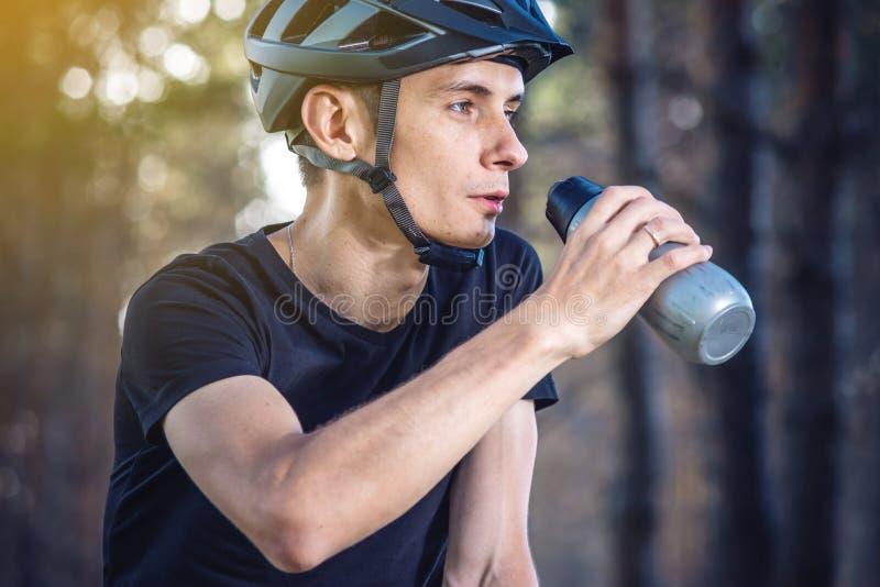 Cyklista w hełm wodzie pitnej od butelki podczas gdy jadący w parku Aktywny i zdrowy styl życia zdjęcia stock