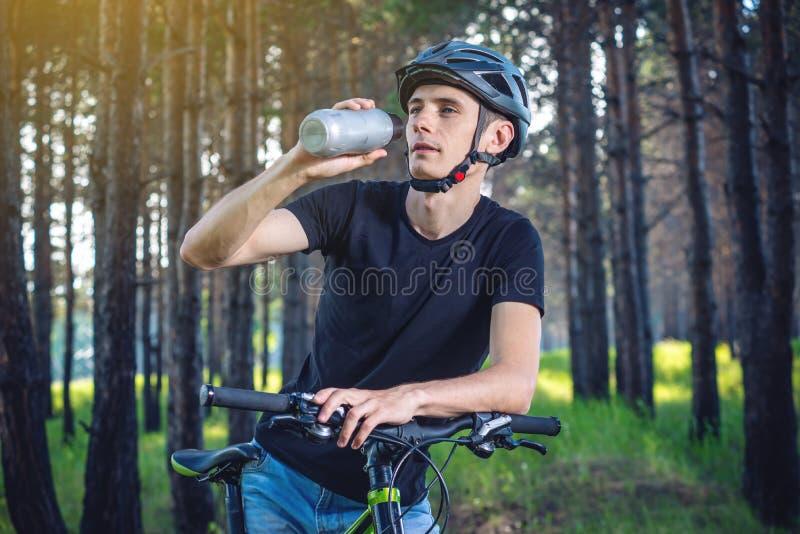 Cyklista w hełm wodzie pitnej od butelki podczas gdy jadący w parku Pojęcie aktywny i zdrowy styl życia zdjęcie stock