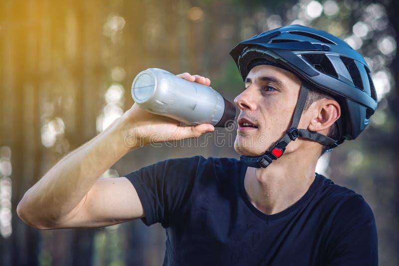 Cyklista w hełm wodzie pitnej od butelki podczas gdy jadący w parku Pojęcie aktywny i zdrowy styl życia zdjęcia stock