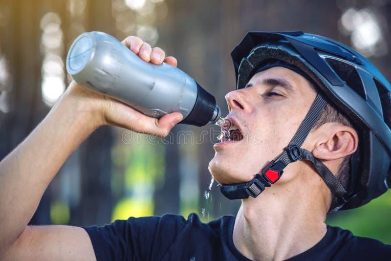 Cyklista w hełm wodzie pitnej od butelki podczas gdy jadący w parku wśród drzew Aktywny i zdrowy styl życia obraz royalty free