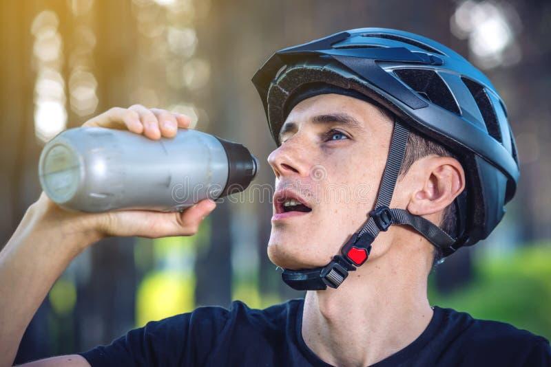 Cyklista w hełm wodzie pitnej od butelki podczas gdy jadący w parku wśród drzew Aktywny i zdrowy styl życia zdjęcie stock