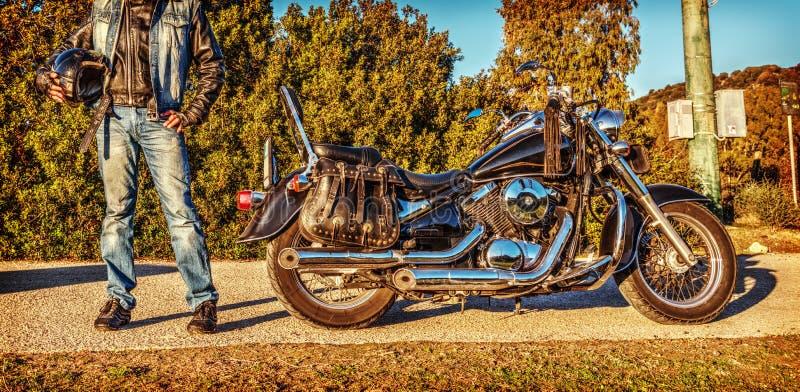 Cyklistanseende vid en klassisk motorcykel royaltyfria foton