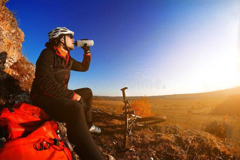 Cyklistdricksvatten för argt land med cykeln, himmelbakgrund Slapp fokus fotografering för bildbyråer