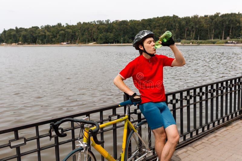 Cyklistdrinkvatten fr?n flaskan Bredvid honom är en vägcykel I bakgrundssj?n arkivfoton