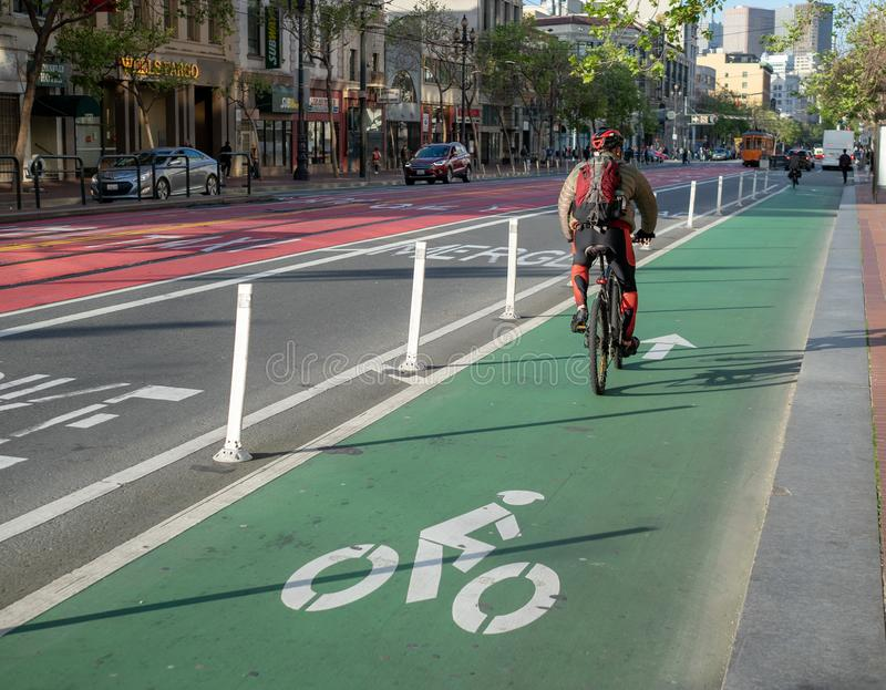 Cyklisten använder en designerad cykelgränd på marknadsgatan på pendlingssträcka fotografering för bildbyråer