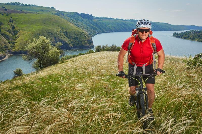 Cyklisten har affärsföretag på hans mountainbike till och med grön äng mot härlig himmel royaltyfria foton