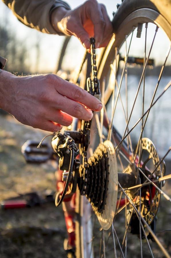 Cyklisten kontrollerar cykelkedjan, når han har kört i parkera royaltyfria bilder