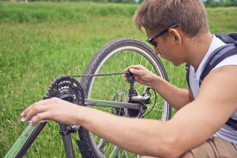 Cyklisten kontrollerar kedjan fotografering för bildbyråer