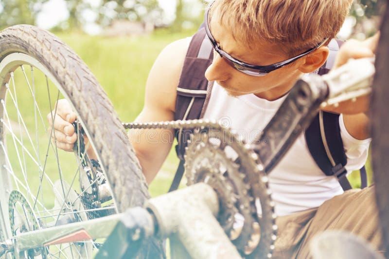 Cyklisten kontrollerar kedjan av cykeln fotografering för bildbyråer