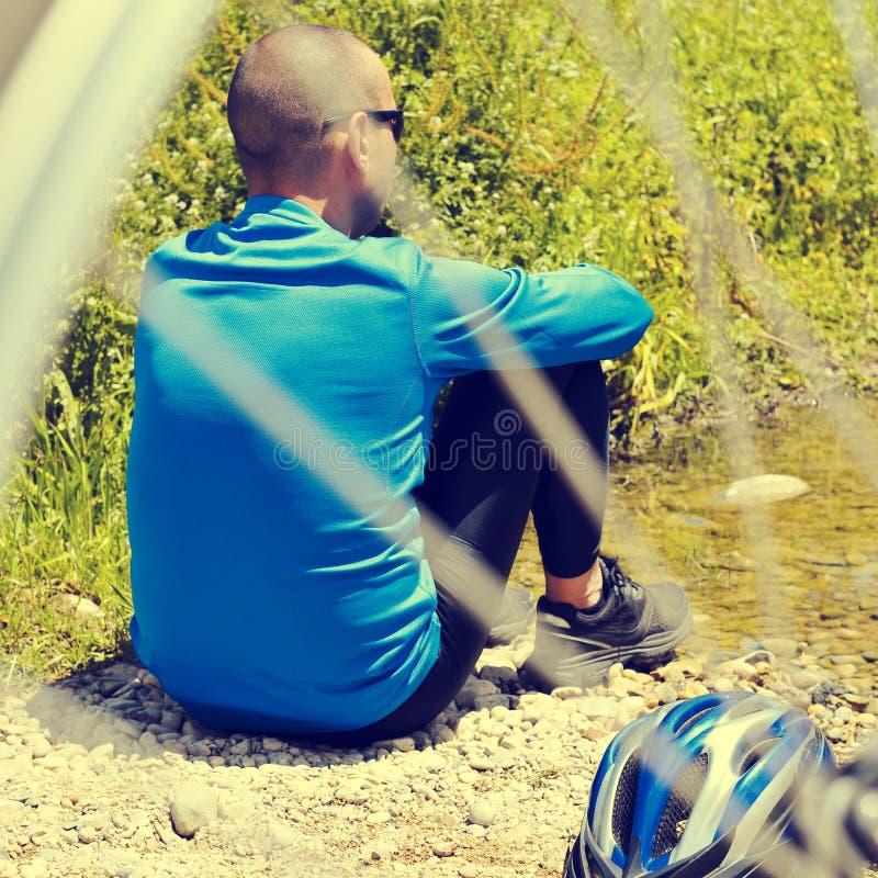 Cyklisten som får något, vilar på flodstranden med ett retro filter e royaltyfria bilder