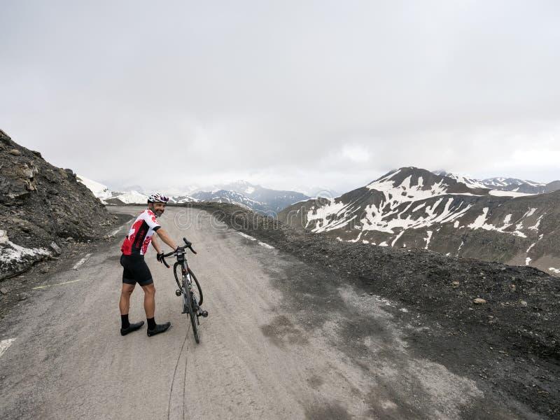 Cyklisten står bredvid hans cykel överst av bergpasserandet sänka de la bonette i de franska fjällängarna royaltyfria bilder