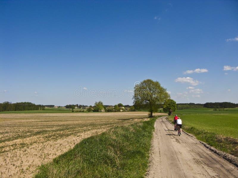 Cyklister i vår- eller sommarsmutsbana royaltyfri bild