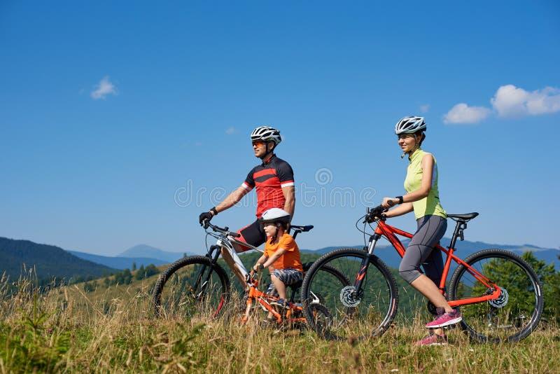 Cyklister, mamma, farsa och barn för ung familj som turist- vilar med cyklar royaltyfria foton