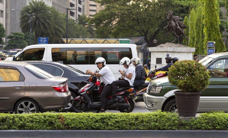 Cyklister och bilar som v?ntar i trafik i Manila, Makati, Filippinerna arkivfoto