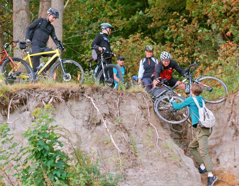 Cyklister och brant kulle, turister att hjälpa sig royaltyfri fotografi