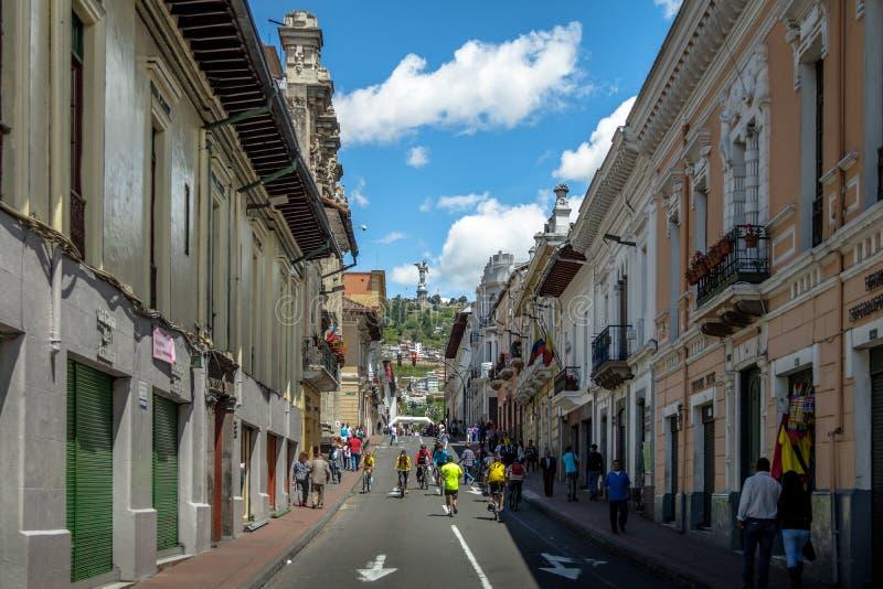 Cyklister och gångare på en söndag stängde gatan av Quito och oskulden Mary Monument överst av kullen för El Panecillo - Quito, E royaltyfri fotografi
