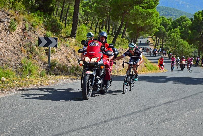 Cyklister som är hållande på till motorcykelLa Vuelta España arkivfoto